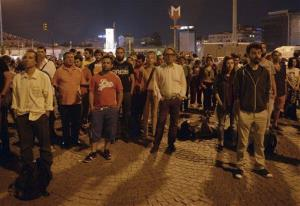 Erdem Gunduz, left, and dozens of people stand silently in Taksim Square in Istanbul, Turkey, early Tuesday, June 18, 2013.