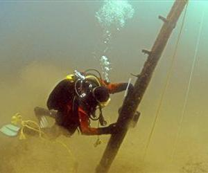 In this photo made June 16, 2013, and provided by Great Lakes Exploation Group, diver Jim Nowka of Great Lakes Exploration Group inspects a wooden beam extending from the floor of Lake Michigan.