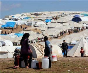 This citizen journalism image provided by Aleppo Media Center AMC shows Syrian refugees filling their buckets at Atmeh refugee camp, in the northern Syrian province of Idlib, Syria.