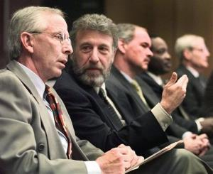 In this Thursday, May 6, 1999 file photo, George Zimmer, second from left, gestures to Andy Dolich prior to a meeting, in Oakland, Calif.