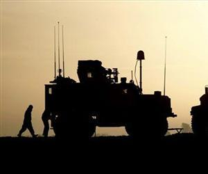 A U.S. soldier walks by MRAP (mine-resistant ambush -rotected) vehicles in Helmand province, southern Afghanistan.