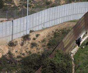 A man walks along the Mexico side of the old border fence as the newer fence sits in the distance, Jan. 29, 2013, in Tijuana, Mexico.