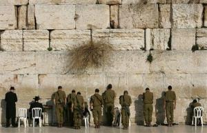 In this Monday, Feb. 12, 2007 file photo, Israeli soldiers and ultra-Orthodox Jewish men pray next to the Western Wall, in Jerusalem.
