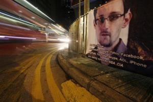 A bus drives past a banner supporting Edward Snowden, in Hong Kong.