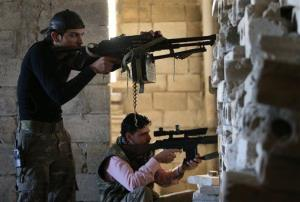 Free Syrian Army fighters take their positions as they observe the Syrian army forces.
