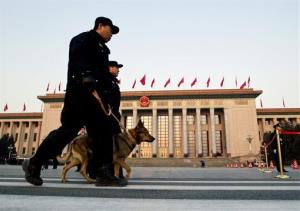 Police officers patrol with a dog while walking past the Great Hall of the People in Beijing.