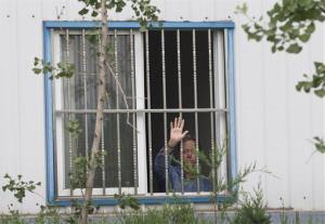 Chip Starnes, co-owner of Specialty Medical Supplies, waves from a window after he was held hostage by workers inside his plant on the outskirts of Beijing.