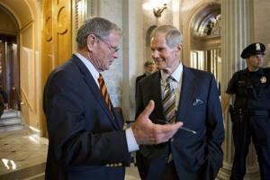 Republican Senator James Inhofe speaks with Democratic Senator Bill Nelson outside the chamber after the immigration bill got more than 60 needed votes to advance in the Senate.