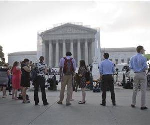People wait outside the Supreme Court in Washington as key decisions are expected to be announced Monday, June 24, 2013.