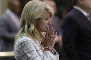 Sen. Wendy Davis, D-Fort Worth, reacts after she was called for a third and final violation in rules to end her filibuster attempt to kill an abortion bill in Austin, Texas.