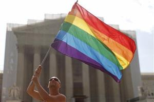 Vin Testa from Washington, waves the rainbow flag in support of gay marriage in front of the Supreme Court in Washington, Monday, June 24, 2013.