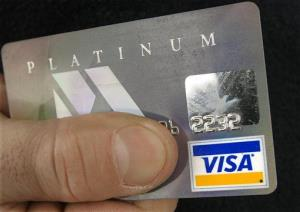 The Visa logo on a card holder's credit card is shown.
