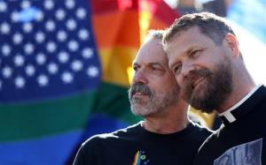 Michael Deschenes, left, and Cary Bass, who had a church wedding and plan to become legally married, stand together at a celebration for the Supreme Court's rulings.