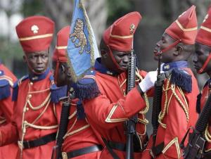 A member of the honor guard adjusts another's collar as they prepare for the arrival of President Barack Obama at the presidential palace in Dakar, Senegal, Thursday, June 27, 2013.