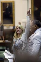 Sen. Wendy Davis, D-Fort Worth, left, who filibustered an abortion bill, reacts as time expires, Tuesday, June 26, 2013, in Austin, Texas.