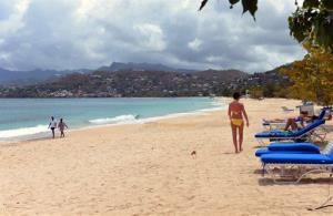 Tourists walk on the white sand of the Grand Anse Beach in Grenada. Hopefully they won't tweet anything bad about it.
