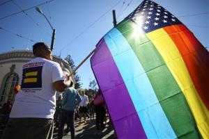 Larry Pascua carries a rainbow flag at a celebration for the US Supreme Court's rulings on Prop. 8 and the Defense of Marriage Act in San Francisco.