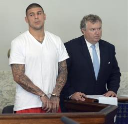 Former New England Patriots tight end Aaron Hernandez, left, stands with his attorney Michael Fee, right, during arraignment in Attleboro District Court Wednesday, June 26, in Attleboro, Mass.