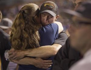 Surviving firefighter Brendan McDonough embraces a mourner near the end of a candlelight vigil in Prescott, Arizona.