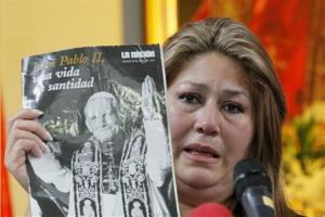 Floribeth Mora holds up a magazine featuring Pope John Paul II on the cover as she gives her account of a miracle attributed to him during a press conference in San Jose, Costa Rica, July 5, 2013.