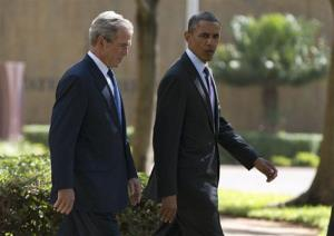 President Barack Obama walks with former president George W. Bush during a wreath laying ceremony to honor the victims of the US Embassy bombing on Tuesday, July 2, 2013, in Dar es Salaam, Tanzania.