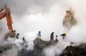 In this Oct. 11, 2001, file photo, firefighters make their way over the ruins of the World Trade Center through clouds of dust.