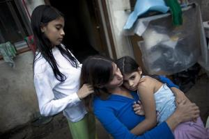 Andrea Nerone, center, sits with daughters Malena, right, and Candela at their home in Buenos Aires. Nerone lost her home and was denied welfare to support her family after her husband abandoned her.