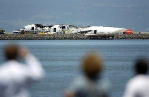 People look at the wreckage of Asiana Flight 214 where it crashed at San Francisco International Airport in San Francisco, Saturday, July 6, 2013.