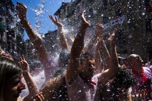 Revelers are sprayed with water thrown from balconies during the launch of the 'Chupinazo' rocket, to celebrate the official opening of the 2013 San Fermin fiestas, Saturday, July 6, 2013 in Pamplona.