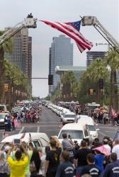 A procession of 19 hearses for the 19 firefighters killed in a wildfire a week ago drives through Phoenix.