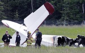Police and emergency personnel stand near the remains the aircraft at the Soldotna Airport in Soldotna, Alaska.