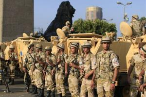 Egyptian army soldiers take their positions near armored vehicles to guard the entrances of Tahrir Square in Cairo today.