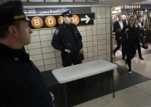 Police officers keep an eye on commuters in a subway station in New York, Tuesday, April 16, 2013.
