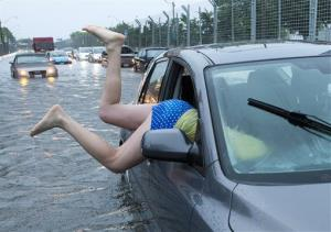 A woman gets back into her flooded car on the Toronto Indy course on Lakeshore Boulevard in Toronto.