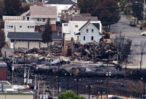Charred tanker cars are piled up in Lac-Megantic, Quebec, Tuesday.