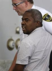 Ernest Wallace, of Miramar, Fla., mouths words to people sitting in Attleboro District Court, in Attleboro, Mass., as he is escorted from the court room after pleading not guilty July 8, 2013.