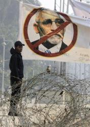 An Egyptian anti-riot soldier stands under a banner showing Muslim Brotherhood leader Mohammed Badie.