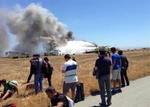 In this Saturday, July 6, 2013, photo provided by passenger Benjamin Levy, passengers from Asiana Airlines flight 214, many with their luggage, are on the tarmac just moments after the plane crashed.