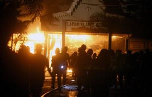 Police officers and firefighters stand outside the front of Tanjung Gusta prison that was set ablaze by inmates during a prison riot in Medan, North Sumatra, Indonesia, Thursday, July 11, 2013.