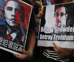 Edward Snowden supporters hold signs during a demonstration outside the US Consulate in Hong Kong, June 15, 2013. The Chinese reads, Say No to Persecutor.