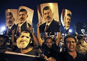 Supporters of ousted Egypt's President Mohammed Morsi hold posters of him as they protest during the Islamic month of Ramadan.