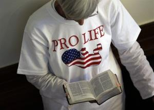 A supporter an abortion bill reads the Bible while in line outside the Texas Senate chambers as he final vote by the Senate is expected to begin, Friday, July 12, 2013.