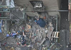Firefighters remove debris from the back of a building in the aftermath of a fire on Thursday, July 11, 2013 in New York City's Chinatown.