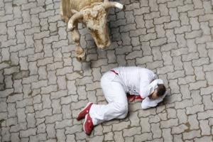 A fallen participant covers his head as a Fuente Ymbro ranch fighting bull approaches him during the running of the bulls of the San Fermin festival, in Pamplona, Spain.