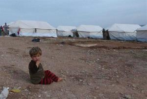 A Syrian child sits on the ground at a refugee camp near the Turkish border with Syria.