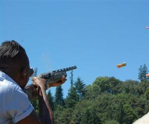 A man fires a shotgun.