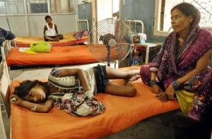 An Indian woman sits beside a child who fell sick after eating a free school lunch, at a hospital in Patna, India, Thursday, July 18, 2013.