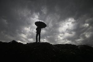 A boy walks with an umbrella to protect himself from the rain in Jammu, India.
