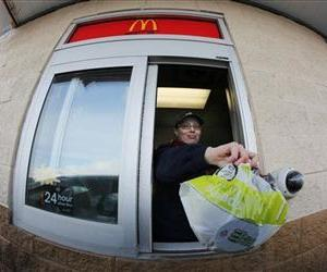 A McDonald's employee hands a patron a salad at the drive up window.