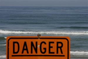 A warning sign is posted on the beach in this 2008 file photo.